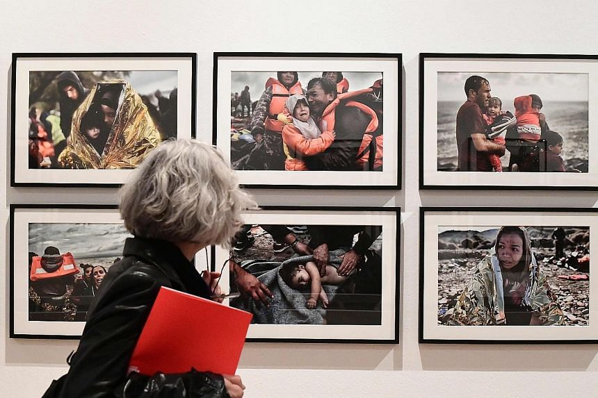 Photos taken during a rescue operation of migrants off the Libyan coast in October last year are on show at The Restless Earth exhibition at Milan's Triennale.