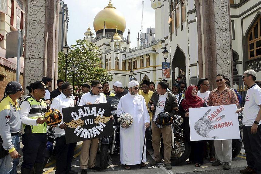 """Mr Amrin Amin (wearing jacket), who arrived in a convoy of bikers from 40 motorcycling groups, with Pergas president Mohamad Hasbi Hassan (in white) and representatives of other Malay/Muslim organisations at the launch of """"Dadah Itu Haram"""" (Drugs are"""