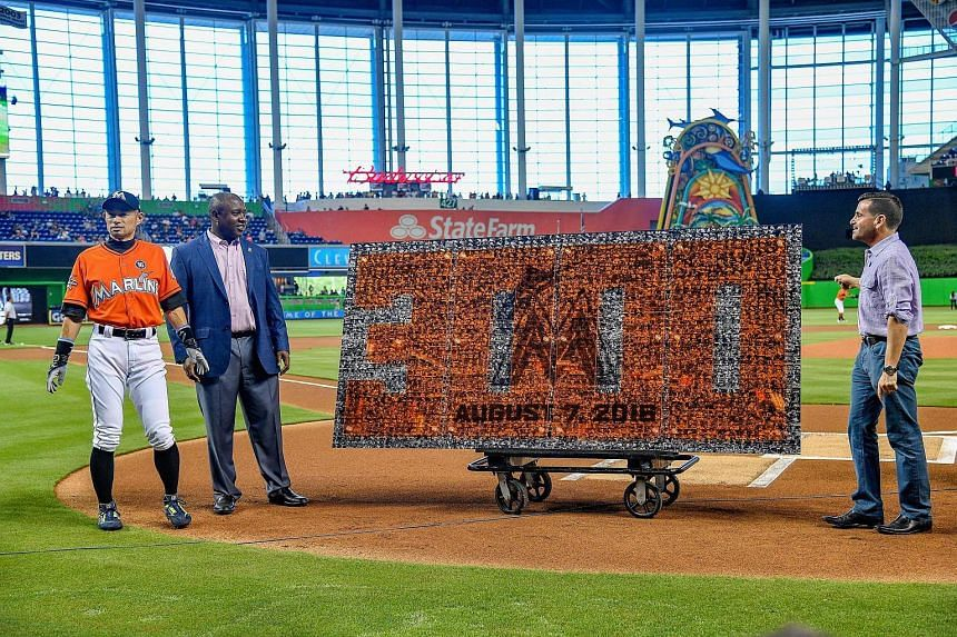 President of the Miami Marlins David P. Samson (right) and President of Baseball Operations Michael Hill (centre) honouring Ichiro Suzuki #51 of the Miami Marlins for his 3000th hit.