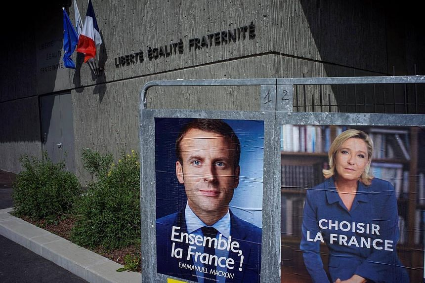 Posters for French presidential election candidates Emmanuel Macron (left) and Marine Le Pen.