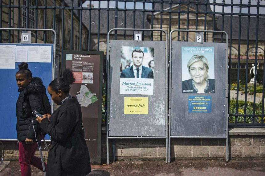 Posters for presidential candidates Emmanuel Macron and Marine Le Pen in Stains, France.