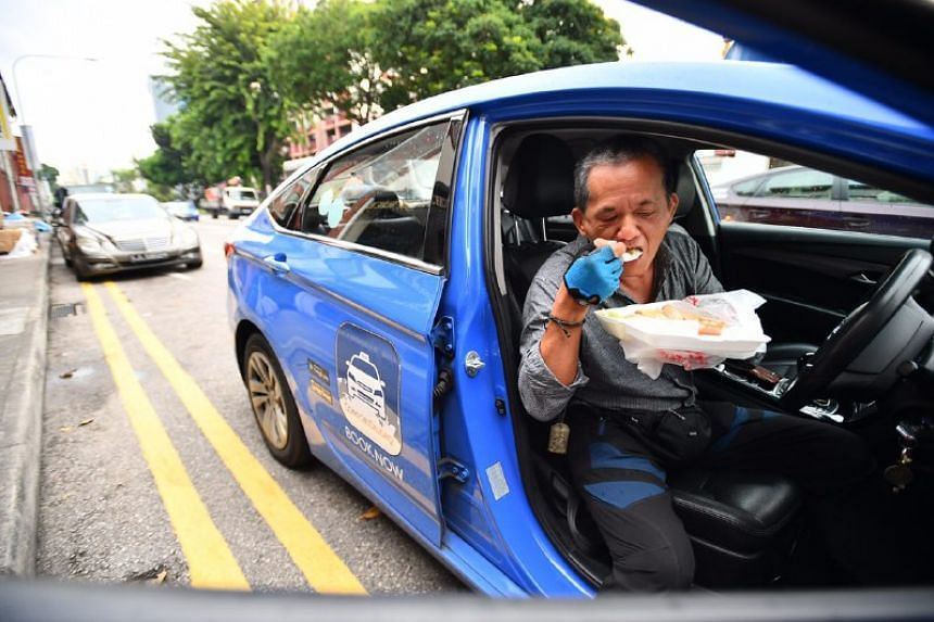 Mr Yu Fook Wah, a 58-year-old taxi driver, eating his free chicken rice at the Serangoon Road outlet on Tuesday (May 2).