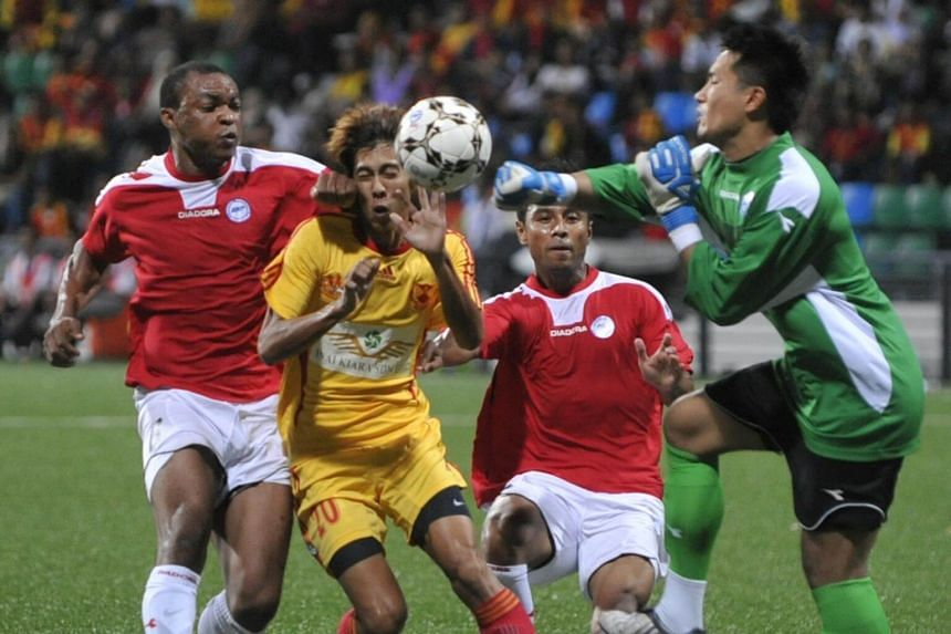 Singapore Selection's goalkeeper Hassan Sunny (in green) punching the ball away from Selangor Selection's attacker Mohd Amirul Hadi during the annual Sultan of Selangor Cup match on Oct 4, 2009 at the Jalan Besar Stadium.