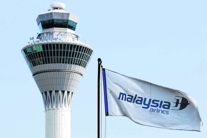 A Malaysia Airlines flag flies in front of the traffic control tower at Kuala Lumpur International Airport.