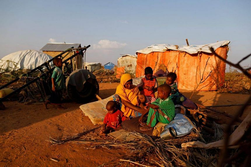 A 29-year-old woman sits with her children beside their shelter at a camp for internally displaced people from drought hit areas in Dollow, Somalia on April 2, 2017.