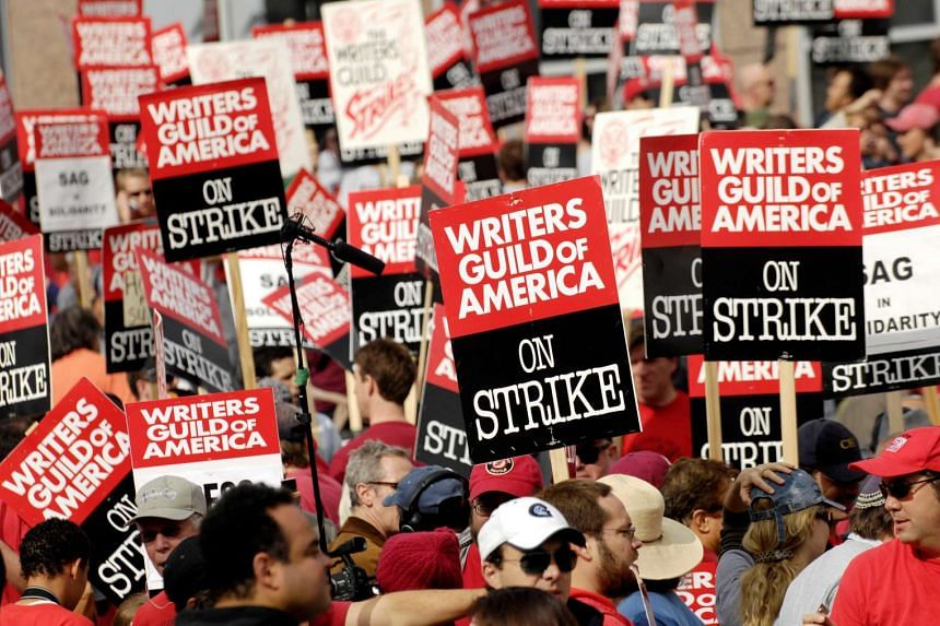 Thousands of Writers Guild of America members and supporters hold signs during a large strike outside Fox studio.