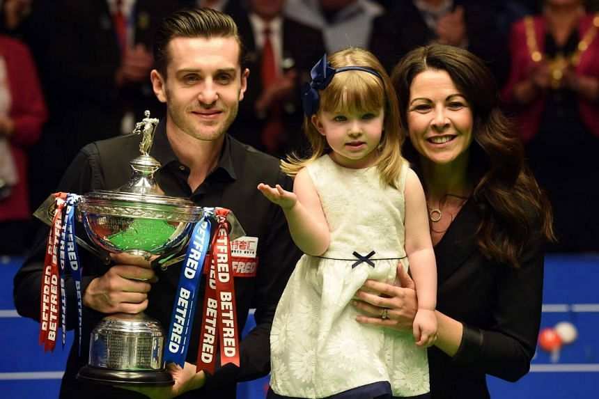 England's Mark Selby poses for a photograph with the trophy, his daughter Sofia Maria and wife Vikki, after beating Scotland's John Higgins in the World Championship Snooker final at The Crucible in Sheffield, northern England on May 1, 2017.