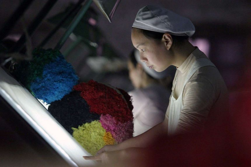 A woman works at a textile factory in Xiangfan, China.