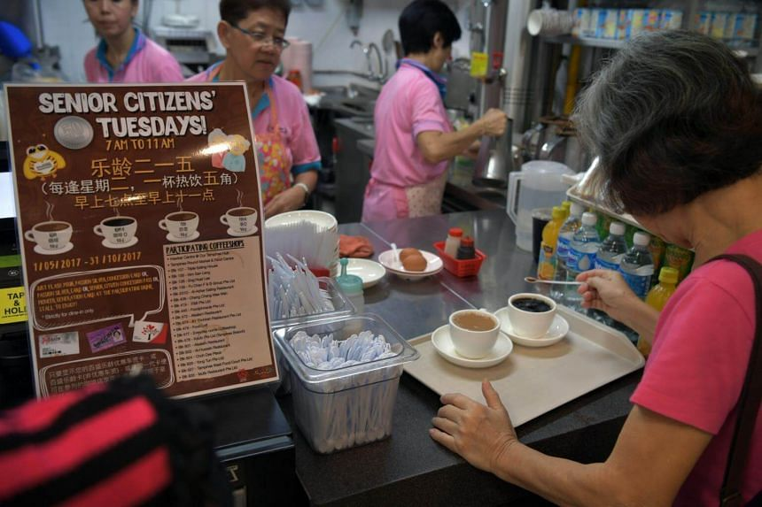 A woman receives her coffee at the drinks stall at the hawker centre of Our Tampines Hub on May 2, 2017.
