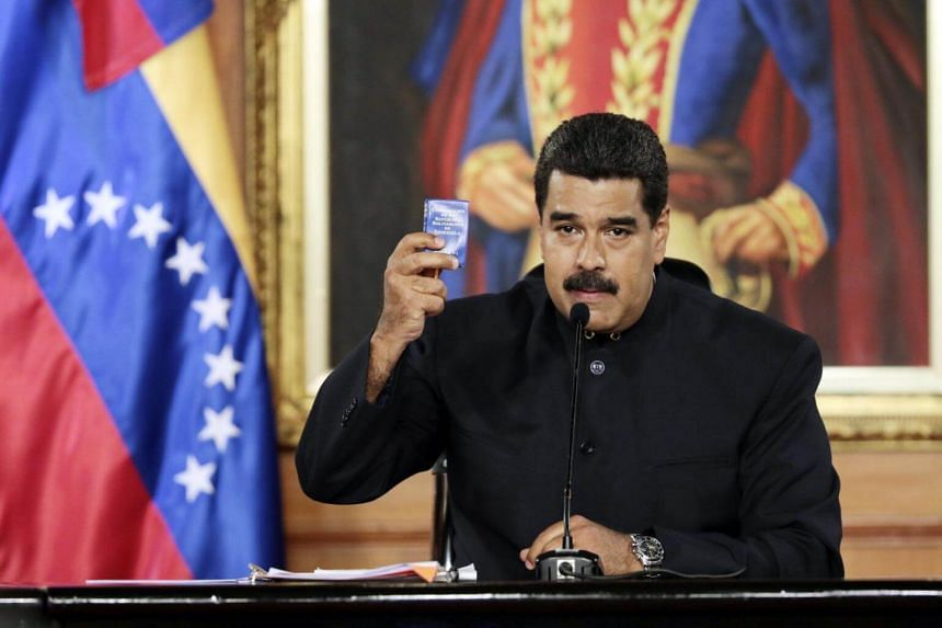 A handout photo made available by the Miraflores Palace's Press Office shows Venezuelan President Nicolas Maduro showing a small copy of the National Constitution in Caracas, Venezuela, on May 01, 2017.