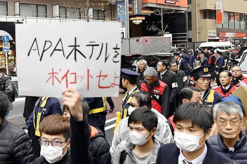 "Chinese residents in Tokyo marching at a protest against the Japanese hotel chain APA Group in February. The owner of the chain came under fire for hate speech earlier this year. A sign reading ""Prime Minister Shinzo Abe"" hanging from a masakaki tree"