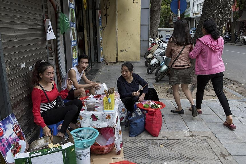 A street vendor in Hanoi, Vietnam. Sidewalk stalls still appeal to people of nearly all social classes in South-east Asia.