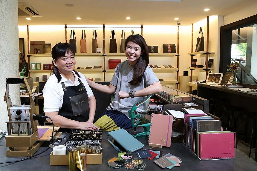 Bynd Artisan employee Tan Buay Heng (far left) with the firm's co-founder Winnie Chan. After working in her family's bookbinding firm Grandluxe for 20 years, Ms Chan launched Bynd Artisan in 2014 to move with the times. Five of Bynd Artisan's craftsm