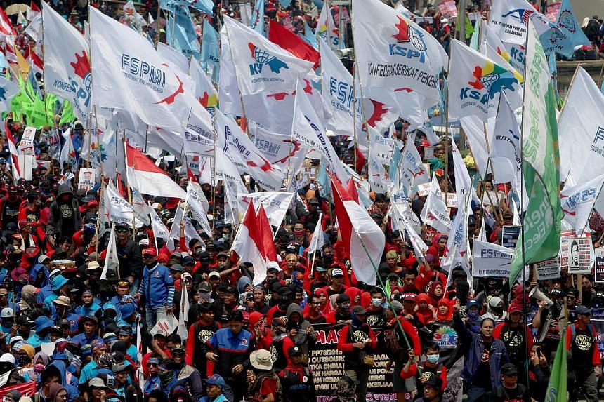 Migrants at a march in Milan, Italy, yesterday. May Day is observed around the world on May 1 to celebrate workers' economic and social achievements and to fight for their rights. Above: Indonesian workers at a rally held to mark May Day in Jakarta y