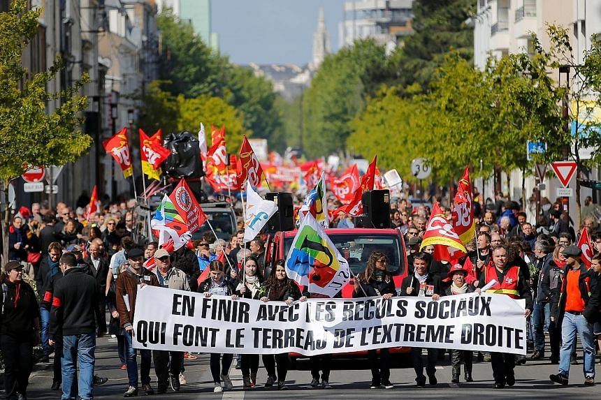"Demonstrators at a May Day march in Nantes, France. The banner reads: ""Finish with social backstepping that makes the ground fertile for the far-right"". The bitterly contested presidential election has polarised France. The latest poll shows Mr Emman"