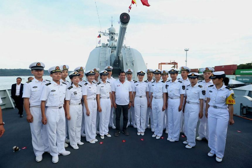 A handout photo showing Filipino President Rodrigo Duterte (centre) joining Chinese Navy officers for a photograph during a tour at a Chinese Naval ship in Davao city, southern Philippines.