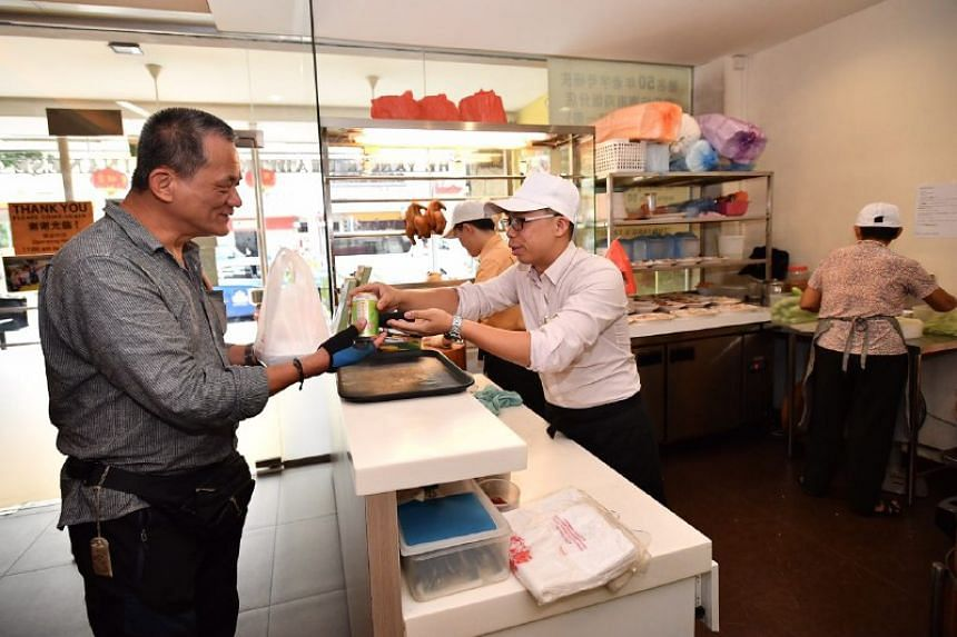 Mr Yu Fook Wah, a 58-year-old taxi driver, receives his free chicken rice at the Serangoon Road outlet on Tuesday (May 2).