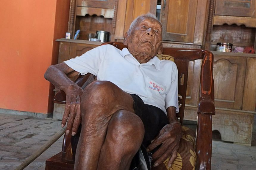 Mbah Ghoto, who has never suffered any severe illness, sits in a chair in his living room.