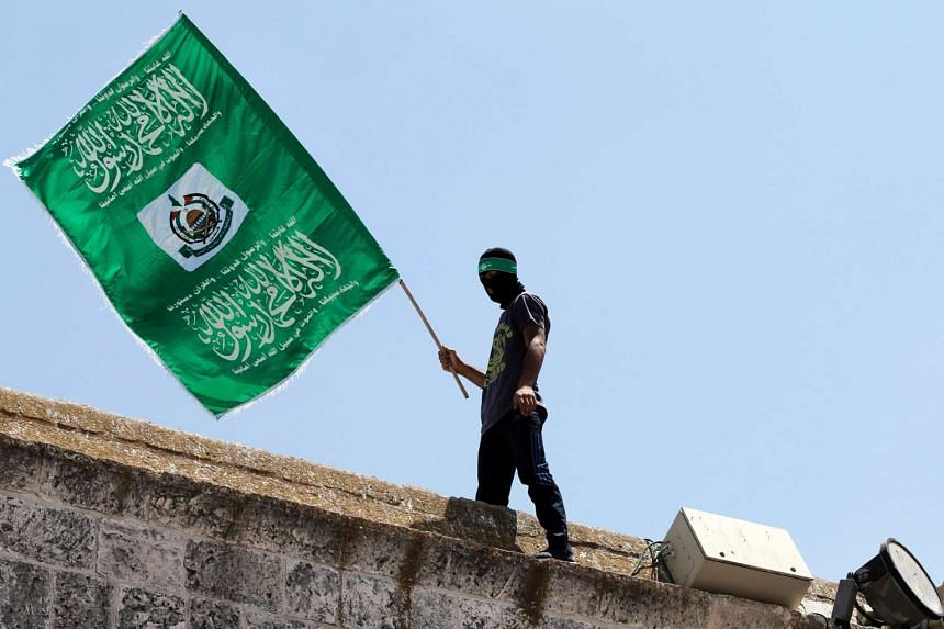 A Palestinian man waves the Hamas flag outside the Dome of the Rock in Jerusalem.