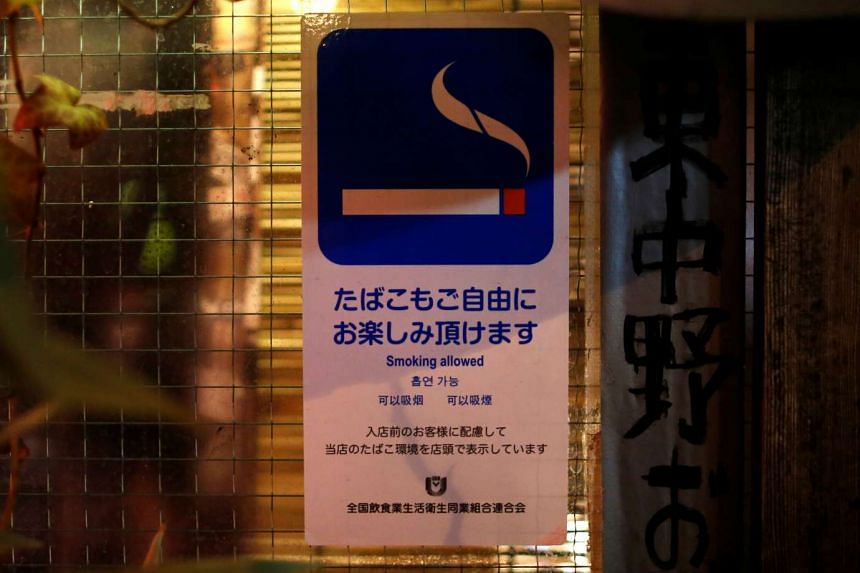 A sign sticker reading 'Smoking allowed' is diplayed outside a pub in Tokyo.