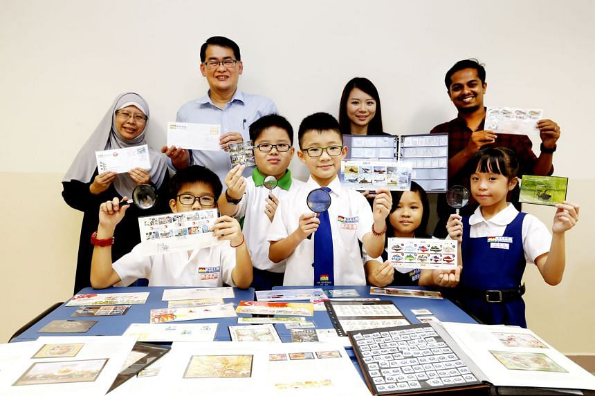 Mee Toh School principal Gau Poh Teck with teachers and pupils showing off their stamp collections. Mr Gau believes in using stamps to impart interesting details that would otherwise be quite dry in a textbook.