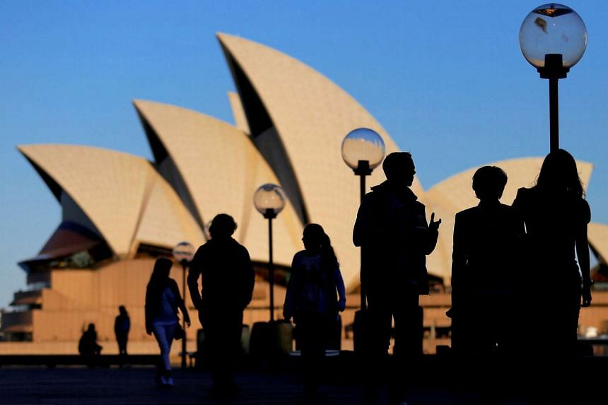 People are silhouetted against the Sydney Opera House at sunset in Australia.
