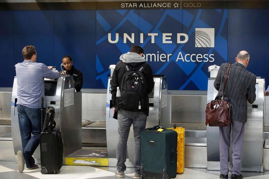 Travellers at the check-in counter at the United Airlines Premier Access in Chicago, Illinois.