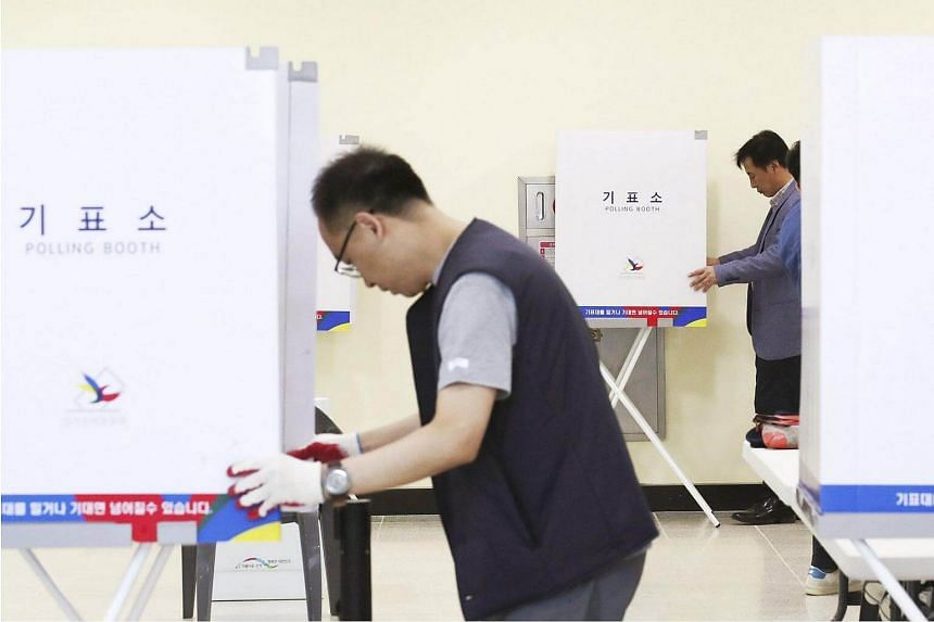 Staff of the Sejong City election committee set up polling booths at a community centre a day before the two-day early voting begins, on May 3, 2017.