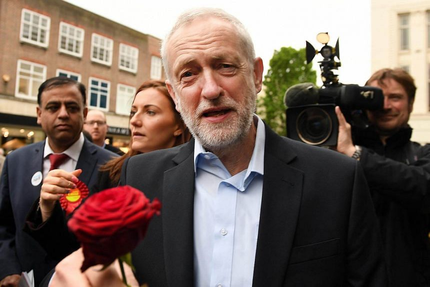 British Labour leader Jeremy Corbyn (centre) with Mohammed Yasin (left), while on the campaign trail in Bedford, on May 3, 2017.