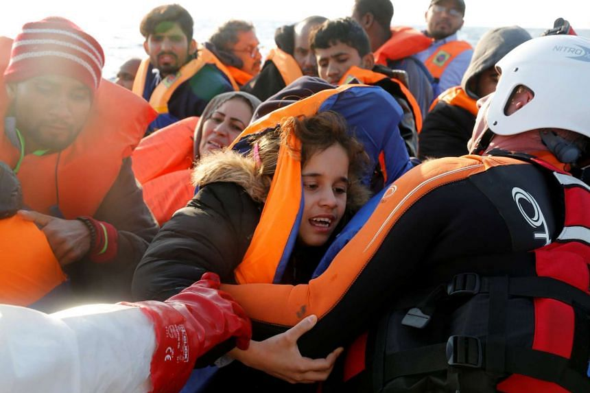 A child migrant is pulled onto a rescue boat in the central Mediterranean Sea, April 5, 2017.
