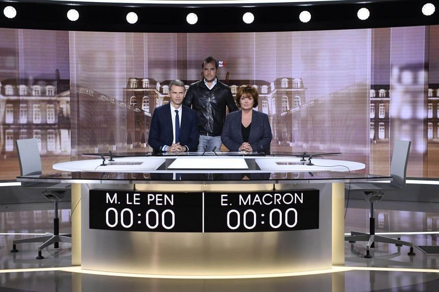 French journalists and TV hosts Christophe Jakubyszyn (left) and Nathalie Saint-Cricq (right) pose with French director Tristan Carne (centre), on the set of the television show where French presidential candidates will hold a debate for the second r