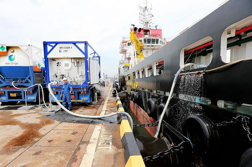 The truck-to-ship LNG bunkering in progress at Jurong Port yesterday. The demonstration, carried out by Pavilion Gas, involved transferring LNG, typically at minus 163 deg C, from two ISO tanks alongside the port's berths to an offshore vessel.