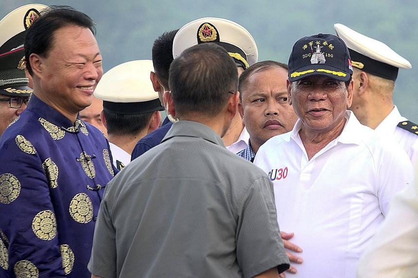 Mr Rodrigo Duterte (wearing cap) with Chinese Ambassador to the Philippines Zhao Jianhua (far left) during a tour of a Chinese naval ship in Davao city, on Monday. Mr Duterte has to assure Beijing that a US visit will not diminish his fondness for Ch