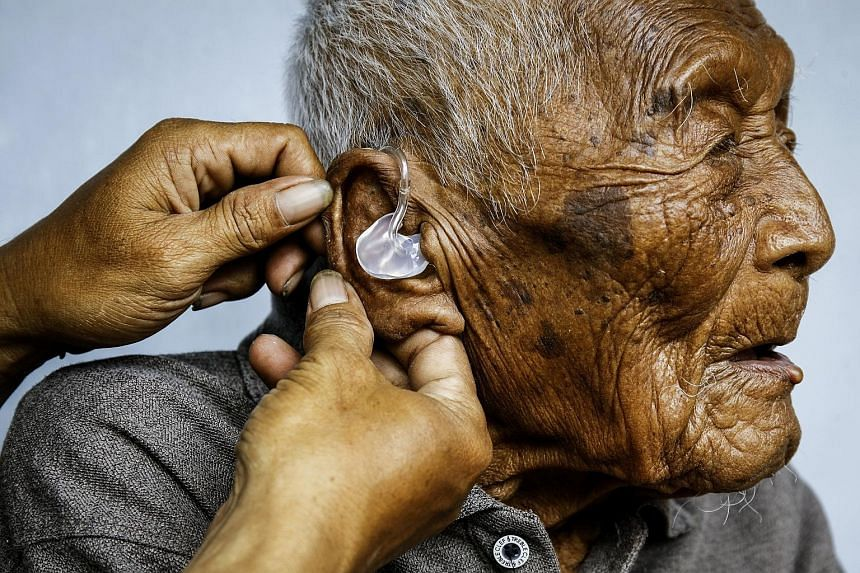 Mr Mbah Gotho getting some help with his hearing aid. The Indonesian claimed he was born in 1870.