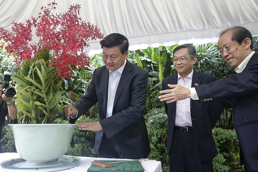 Above: Laos Prime Minister Thongloun Sisoulith at an orchid naming ceremony at the National Orchid Garden yesterday, where the Renanthera Thongloun Sisoulith was named after him. With him are Health Minister Gan Kim Yong (centre) and National Parks B