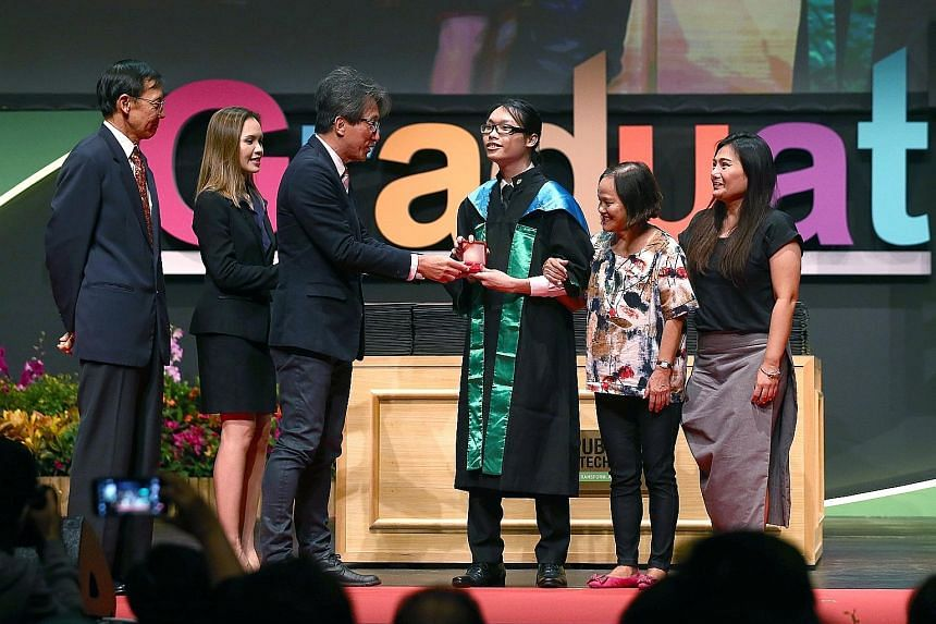 Mr Clive Chia Chun receiving the Lee Kuan Yew Award for Mathematics and Science from Manpower Minister Lim Swee Say at Republic Polytechnic. He was accompanied by his grandmother Goh Hiong Guat, 66, and mother Lilin Ng, 47. With them is Mr David Wong