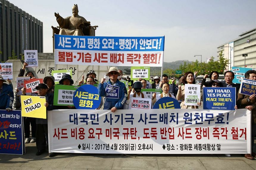 Protesters displaying placards during a demonstration against the deployment of the US military's Thaad defence system, in Seoul on April 28, 2017.