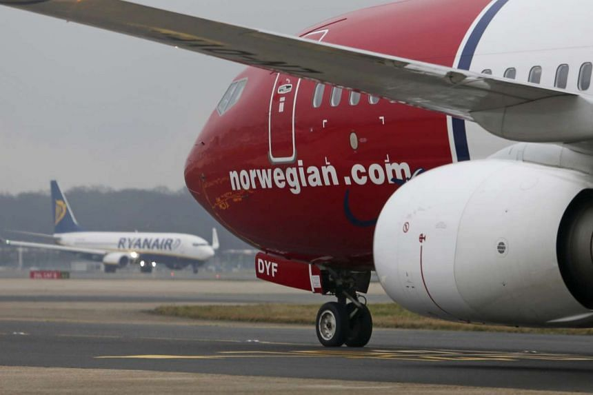 A Boeing 737-800 aircraft, operated by Norwegian Air Shuttle AS, passes a Ryanair Holdings Plc aircraft.