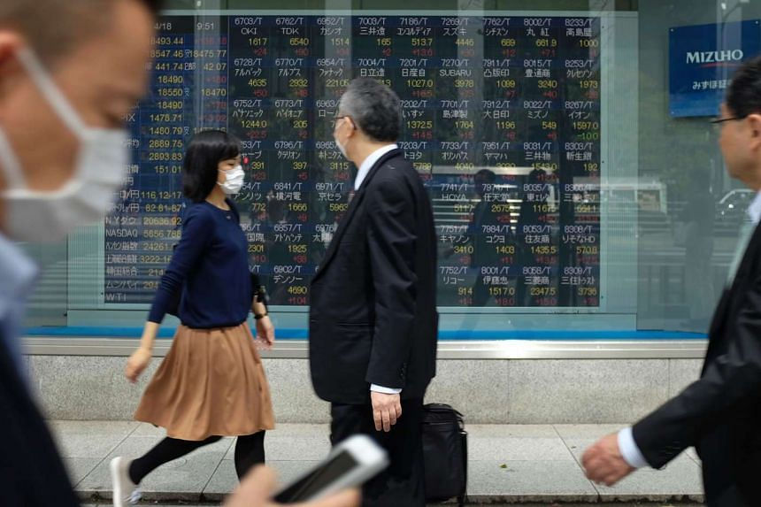 Pedestrians walking in front of a quotation board flashing the Nikkei key index of the Tokyo Stock Exchange in Tokyo.