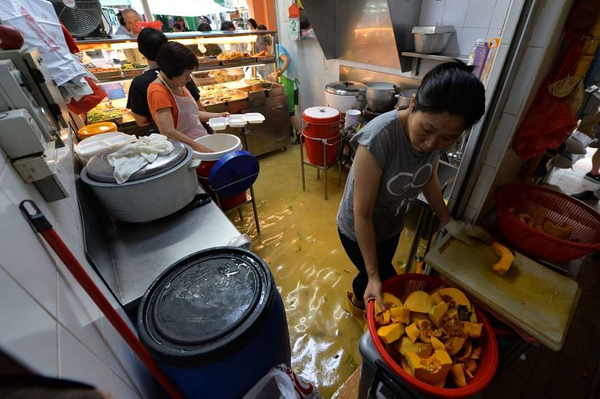 Waste water at a mixed vegetable rice stall. Business was badly affected at a hawker centre in Toa Payoh on Wednesday when waste water overflowed out of a blocked pipe.