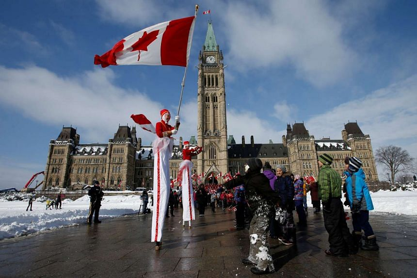 People enjoy a National Flag of Canada Day ceremony on Parliament Hill in Ottawa, Canada, Feb 15, 2017.