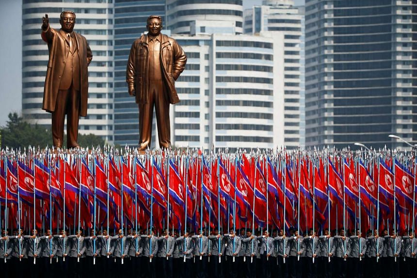 A military parade takes place in Pyongyang in front of statues of North Korea founder Kim Il Sung (left) and late leader Kim Jong Il.