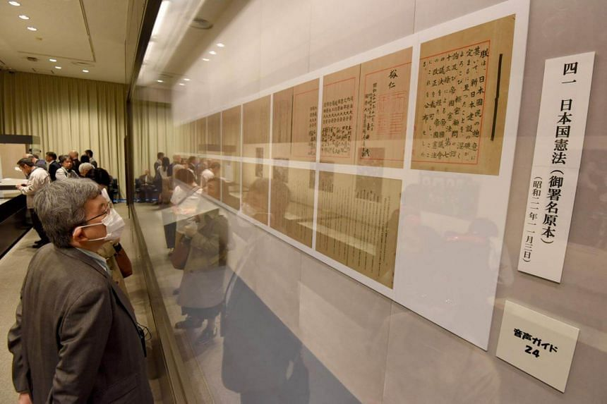 People look at the original and copies of the Japanese Constitution during an exhibition to commemorate its 70th anniversary, at the National Archives of Japan in Tokyo on May 2, 2017.