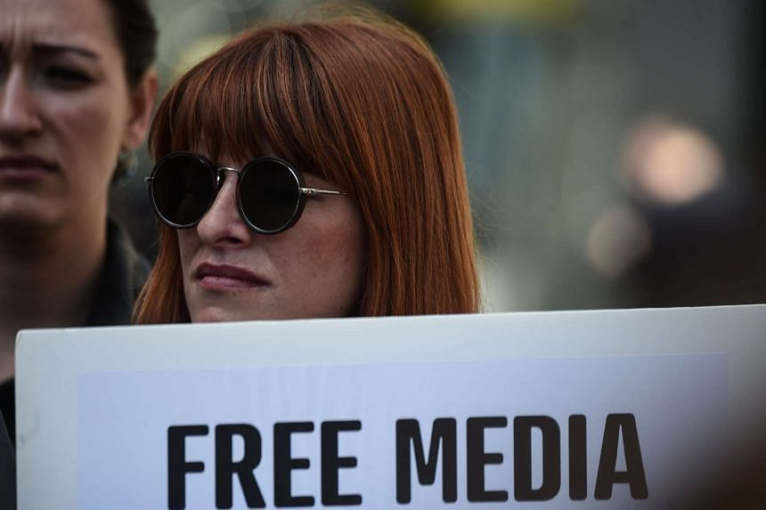 """A journalist holds a placard reading """"free media"""" during a demonstration for the World Press Freedom Day in Istanbul, on May 3, 2017."""