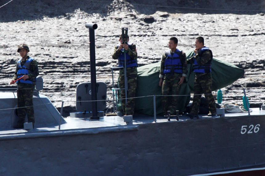 North Korean soldiers observe from a vessel on the Yalu river, near the Chinese border city of Dandong, on May 2, 2017.