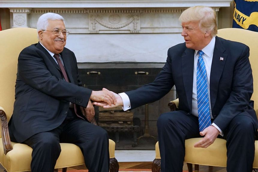 Trump and Abbas shake hands in the Oval Office of the White House.
