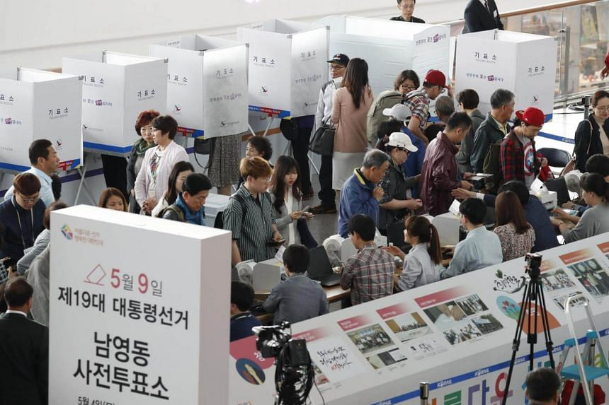 South Koreans receive their ballots at a polling station in Seoul, South Korea on May 4, 2017.