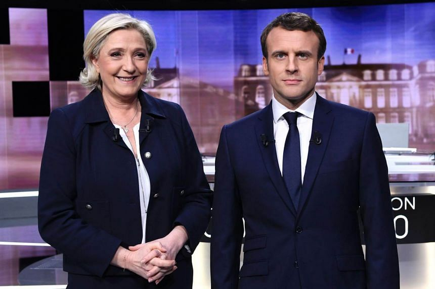 French presidential election candidates Marine Le Pen (left) and Emmanuel Macron (right) pose at a television studio on May 3, 2017.