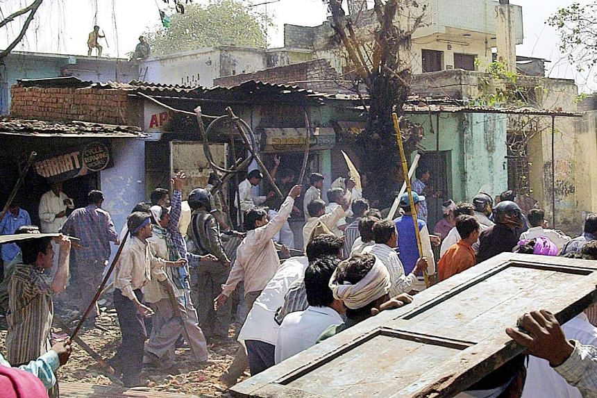 A mob of Indian Hindus armed with swords as they run down a street in the Bapunagar Area of Ahmedabad on March 2, 2002.