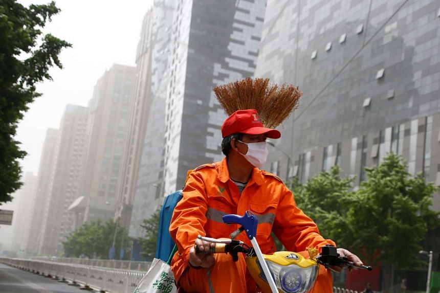 A street cleaner wears a face mask as a dust storm hits Beijing, China on May 4, 2017.